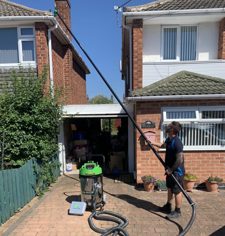 A picture of gutter cleaning services being carried out on a house by ProJet, using a gutter vacuum.