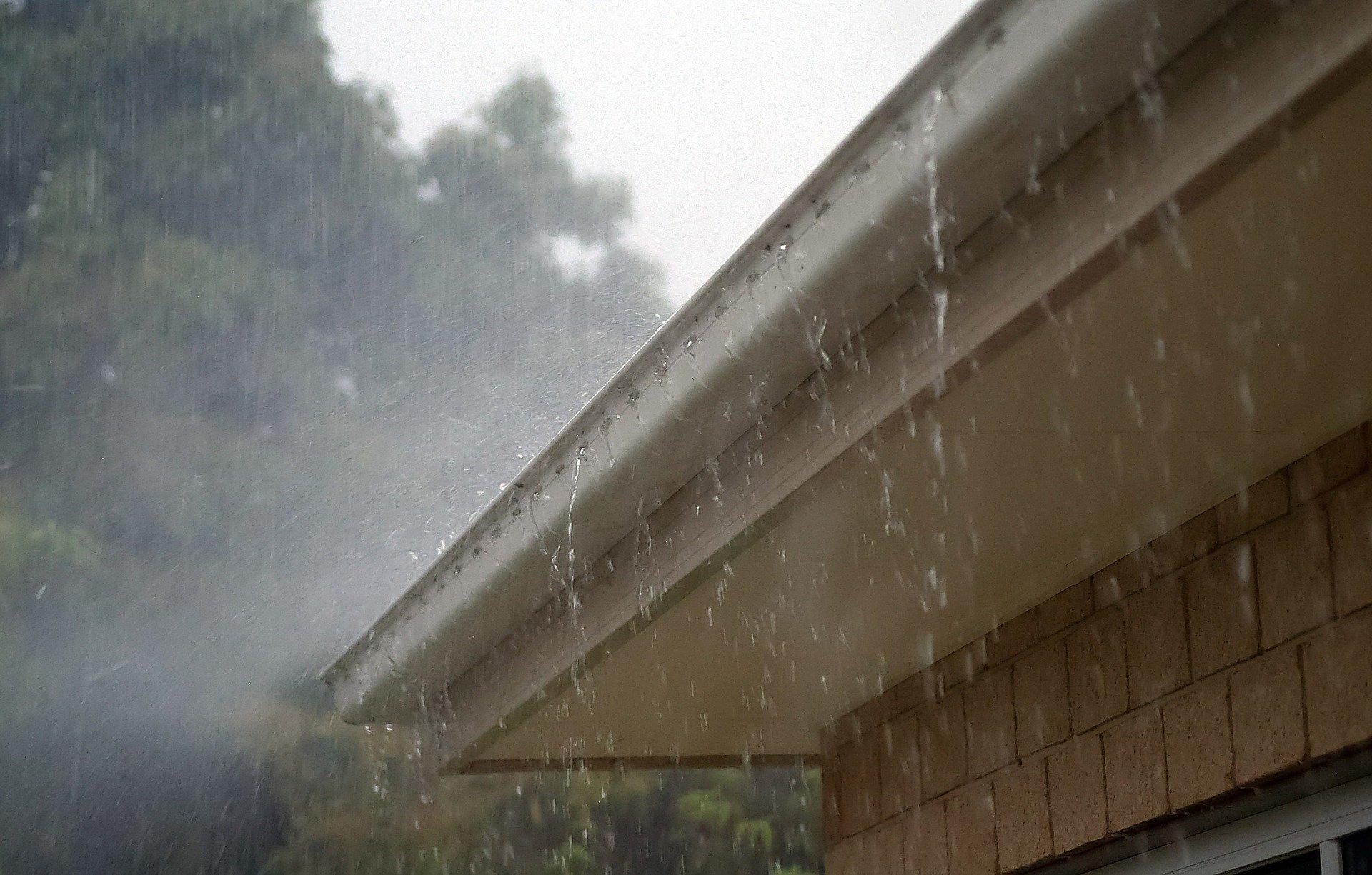 Rain falling down onto a white house gutter